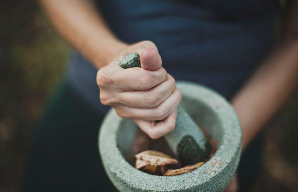 Naturheilkunde mit Kräuter in einem Mörser für Ätherische Öle, Homöopathie, Bachblüten und Schüssler Salze.