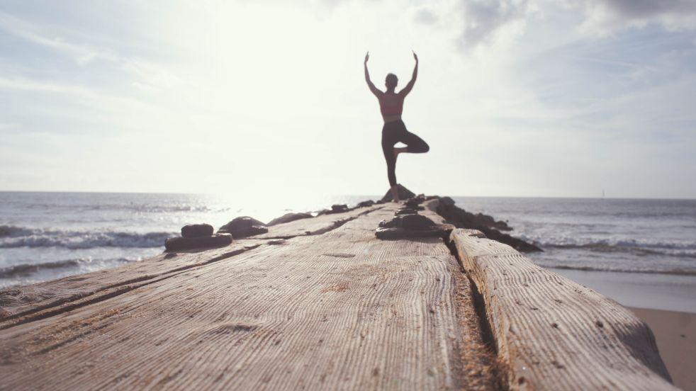 Eine Frau steht auf einem Steg am Meer und fördert durch Sport und Atemtherapie ihre Gesundheit und beugt Erkrankungen wie Arthrose vor.