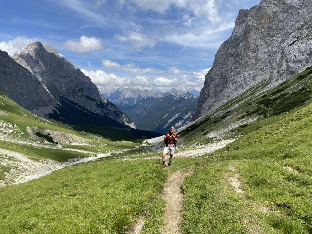 Eine junge Frau steht auf einer grünen Bergwiese, im Hintergrund ein Alpental. Über mich - Heilpraktikerin Dresden Naturheilpraxis Adele Tschech.