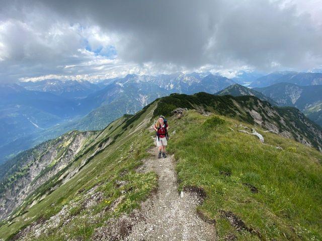 Eine Frau wandert auf dem Grat eines Berges, umgeben von Bergwiese und Berglandschaft.