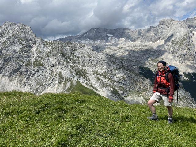 Eine Frau steht auf einer Bergwiese vor einer Gebirgskette.